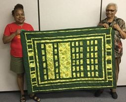 Meredith Coleman McGee and Hazel Hall holding a quilty made by Hazel Hall